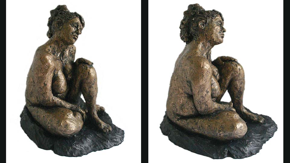 Small clay figure of Gwen seated with her left knee raised.